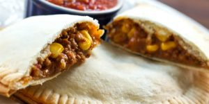 Image of beef and corn filling in a pastry crust with salsa in the background