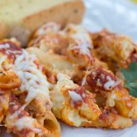 Quick and Easy Baked Ziti on a white plate with garlic bread