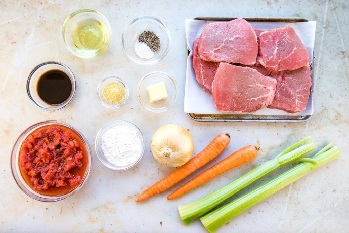Photo is ingredients in separate clear glass bowls: diced tomatoes, Worcestershire sauce, oil, salt and pepper, dry mustard, flour, butter. There are 6 beef steaks on a metal pan. An onion, two carrots, and two stalks of celery are on the counter next to the pan.