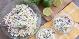 Overhead shot of a large serving bowl of coleslaw with two smaller filled salad dishes and limes and cilantro tothe side