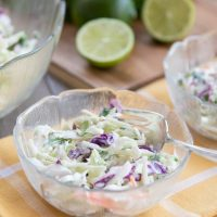 Large serving bowl of coleslaw with two smaller filled salad dishes and limes and cilantro behind the bowls