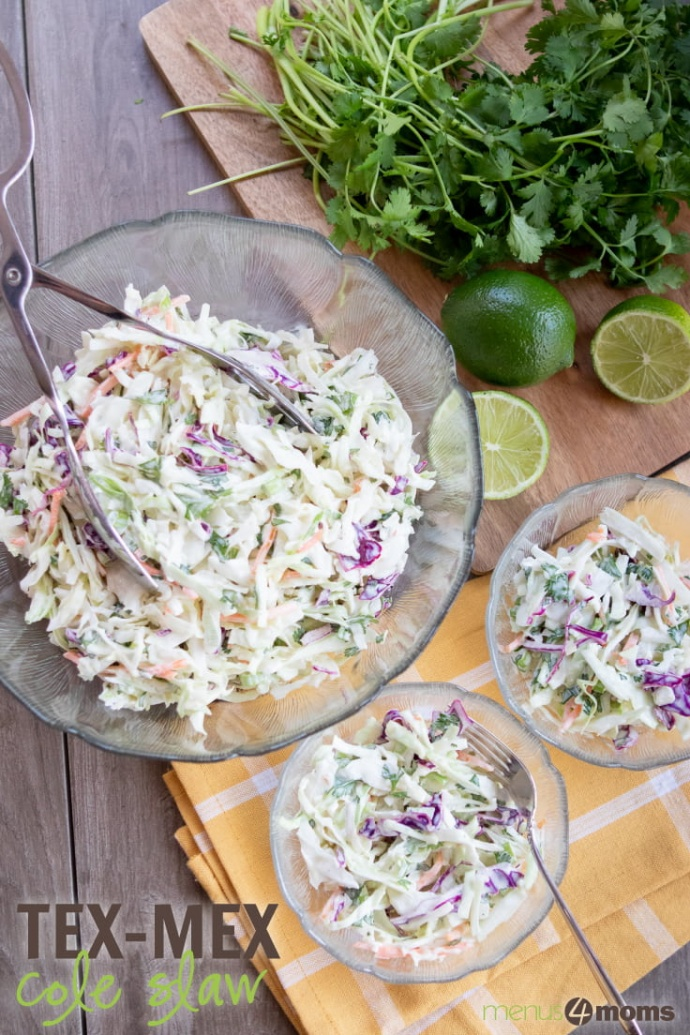 Overhead shot of a large serving bowl of coleslaw with two smaller filled salad dishes and limes and cilantro tothe side; text Tex-Mex Coleslaw Menus4Moms