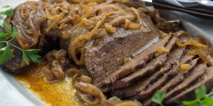 Slices of beef on a white platter. Beef is covered with cooked onions and resting in an au jus. The plate is garnished with parsley and there is a steak knife resting on the back of the platter.