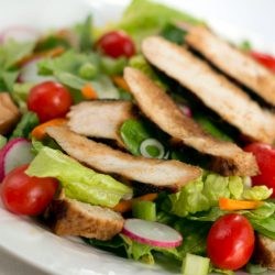 Salad of romaine lettuce pieces, grape tomatoes, and carrots topped with sliced grilled chicken