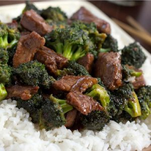 Beef slices with broccoli in a soy-based sauce served over white rice on a white plate with chopsticks to the side