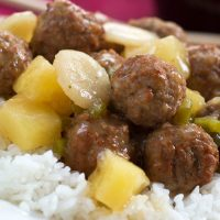 Meatballs, water chestnuts, and pineapple chunks in sauce over white rice, text Sweet and Sour Meatballs #quickandeasy