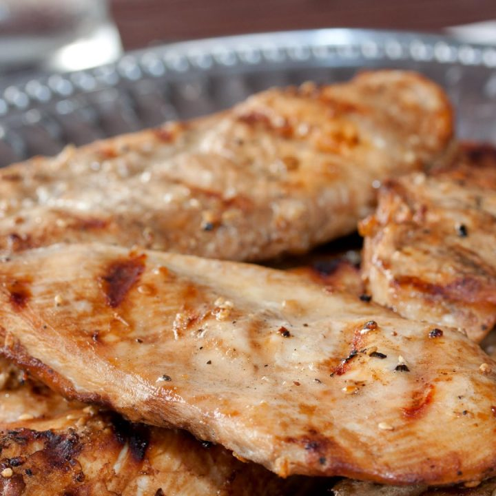 Grilled boneless skinless chicken breasts with a sesame marinade brushed on them and served on a Armetale platter