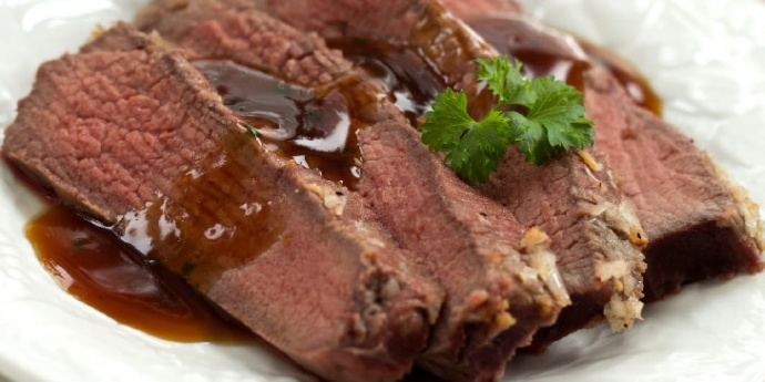 Sliced beef roast on a platter with gravy on top and garnished with parlsey