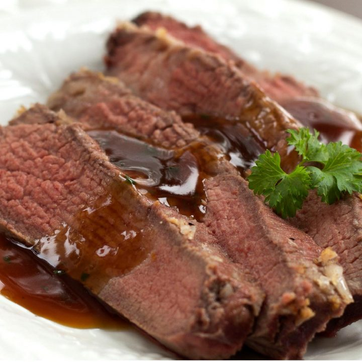 Four slices of sliced roast beef on a white plate with brown gravy on top. Garnished with a sprig of parsley