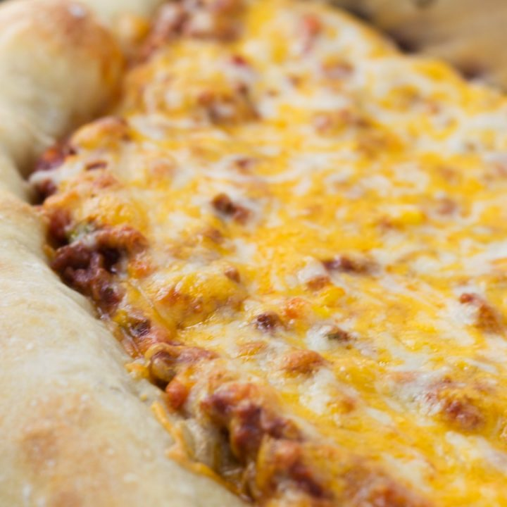 Side view of a whole pizza with sloppy joe sauce covered with colby-jack cheese on a thick crust