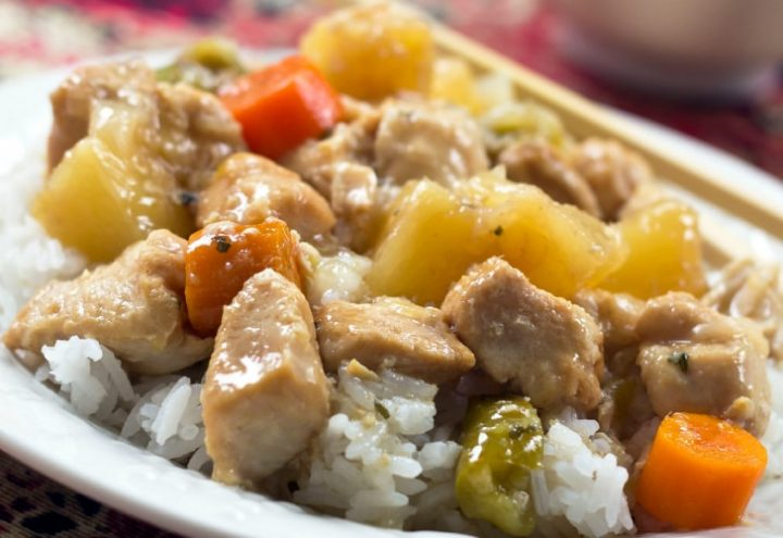 Chunkcs of cooked chicken, pinapple, carrots, and peppers served over white rice
