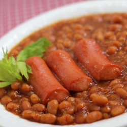 Baked beans in a white bowl with three hot dogs.