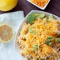 White bowl with rotini pasta, broccoli, and shredded cheddar cheese, next to lemons and a bowl of shredded cheese