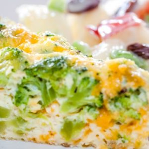 Slice of crustless broccoli quiche on a plate with apple salad