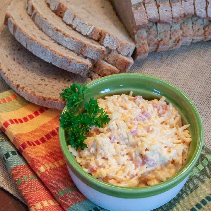 Homemade Pimento Cheese in a green and white bowl, garnished with a sprig of parsley. There is an unpackaged loaf of sliced bread at the top of the photo.