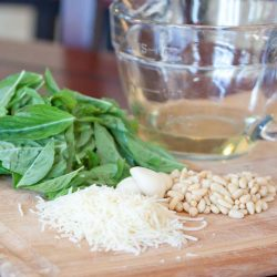 Photo is a pile of basil leaves, a glass measuring cup with olive oil, a pile of shredded parmesan cheese, garlic cloves, and a pile of pine nuts, on a wooden cutting board.