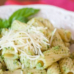 Rigatoni on a white plate topped with shredded parmesan cheese and pesto.