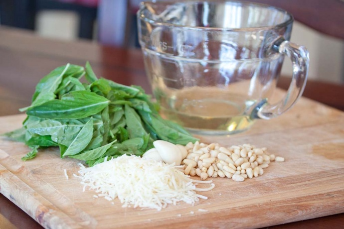 a cutting board with a pile of basil leaves, cloves of garlic, a pile of pine nuts, a pile of shredded Parmesan cheese, and a measuring cup with oil