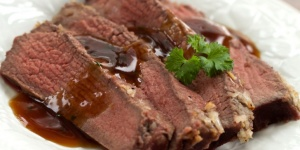 Roast Beef with Picante Sauce garnished with parsley on white plate