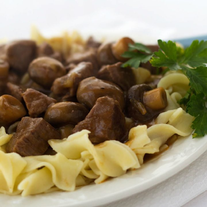 White plate with egg noodles topped with beef and mushrooms, garnished with a sprig of parsley.