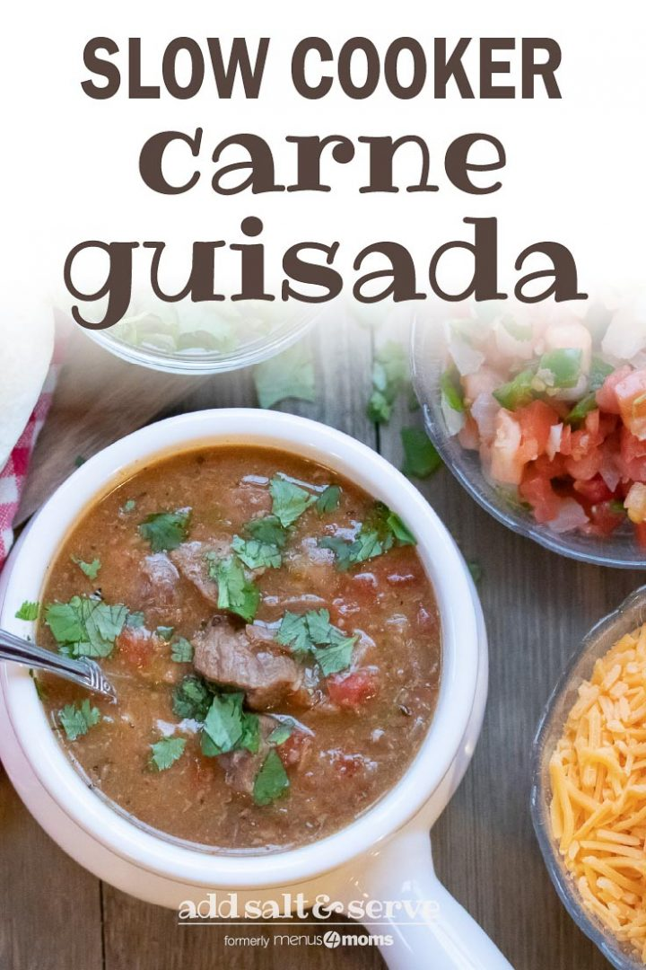 Carne Guisada (Mexican Beef Stew) in a white crock with cheese, tortillas, and pico de gallo. Text Slow Cooker Carne Guisada Add Salt & Serve formerly Menus4Moms