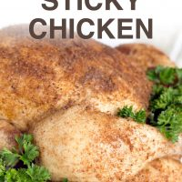 Whole cooked chicken covered with spices, on a white plate garnished with a lot of parsley. Text Slow Cooker Sticky Chicken Add Salt & Serve formerly menus4moms
