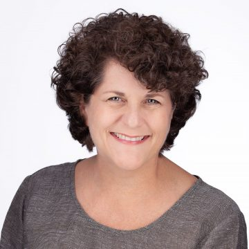 Mary Ann Kelley (white woman with green eyes and short curly brown hair in a gray shirt)