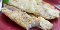 Tilapia fillets on a red plate garnished with parsley