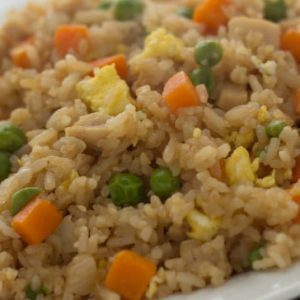 Chicken Fried Rice with carrots, peas, egg, and chicken mixed in with the rice on a white plate