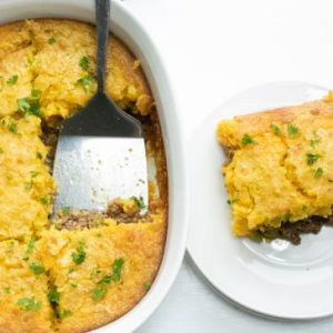 Casserole with ground beef topped with cornbread layer serving on plate with casserole to the left