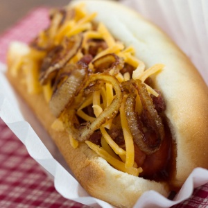 hot dog in bun topped with sauteed onion and grated cheddar cheese.