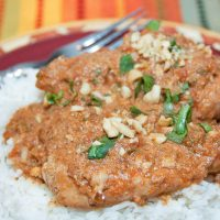 Chicken breasts cooked with peanut sauce over white rice and garnished with chopped cilantro and peanuts