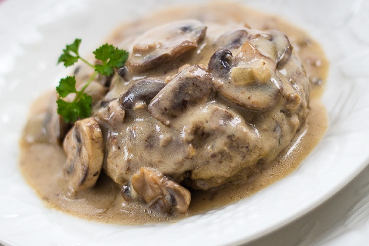 Mushroom Salisbury Steak on a white plate garnished with a sprig of parsley.