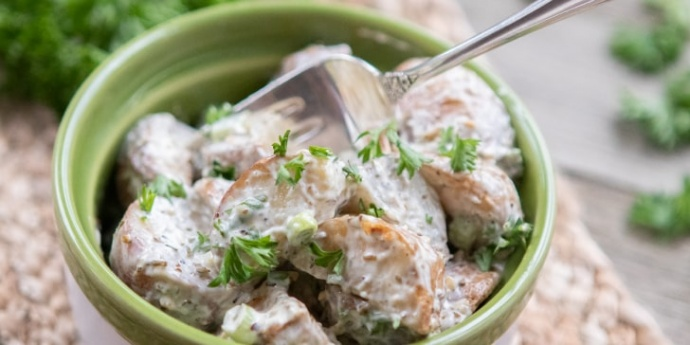 Bowl of potato salad garnished with parsley with a fork