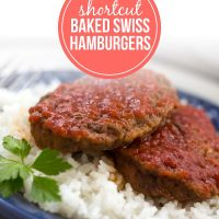 Two Baked Swiss Hamburgers on a bed of rice on a plate.