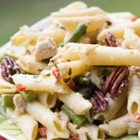 Penne pasta with chopped asparagus, chopped chicken breast, pecans, and chopped red bell pepper