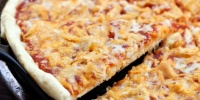 Slice of pizza topped with chicken, cheddar cheese, and barbecue sauce being lifted from the pie.