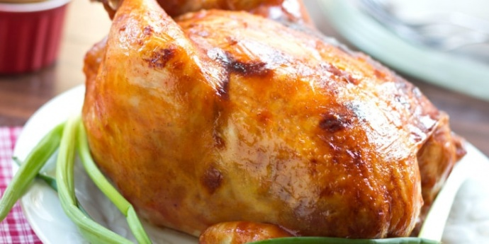 Roasted barbecue chicken on platter garnished with green onion