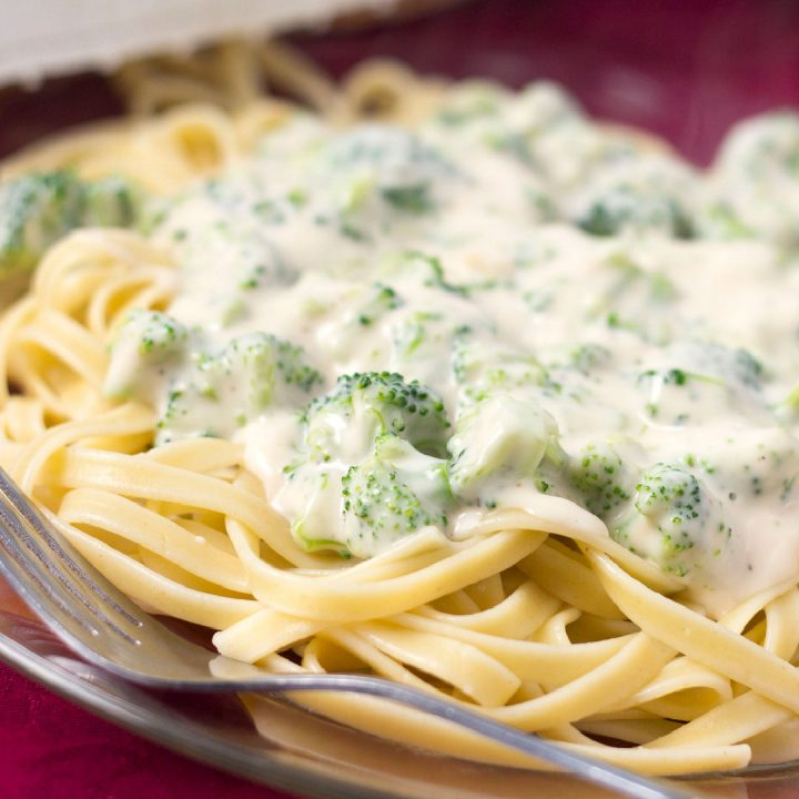 Afredo sauce with broccoli over fettuccine on a clear glass plate with a fork