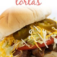 White bun piled with grilled flap meat, lettuce, tomato, cheese, and jalapeno slices. Text is Carne Asada Tortas - Add Salt & Serve logo