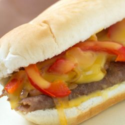 Sliced steak on a white hoagie bun topped with slices of cooked red pepper and onion and topped with cheddar cheese sauce
