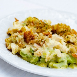 Chicken and broccoli with sauce and bread topping on a white plate