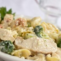 Sliced chicken breast and broccoli with bow tie pasta in a white sauce