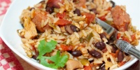 White bowl and fork with rice, black beans, sausage, tomatoes, and green chilies