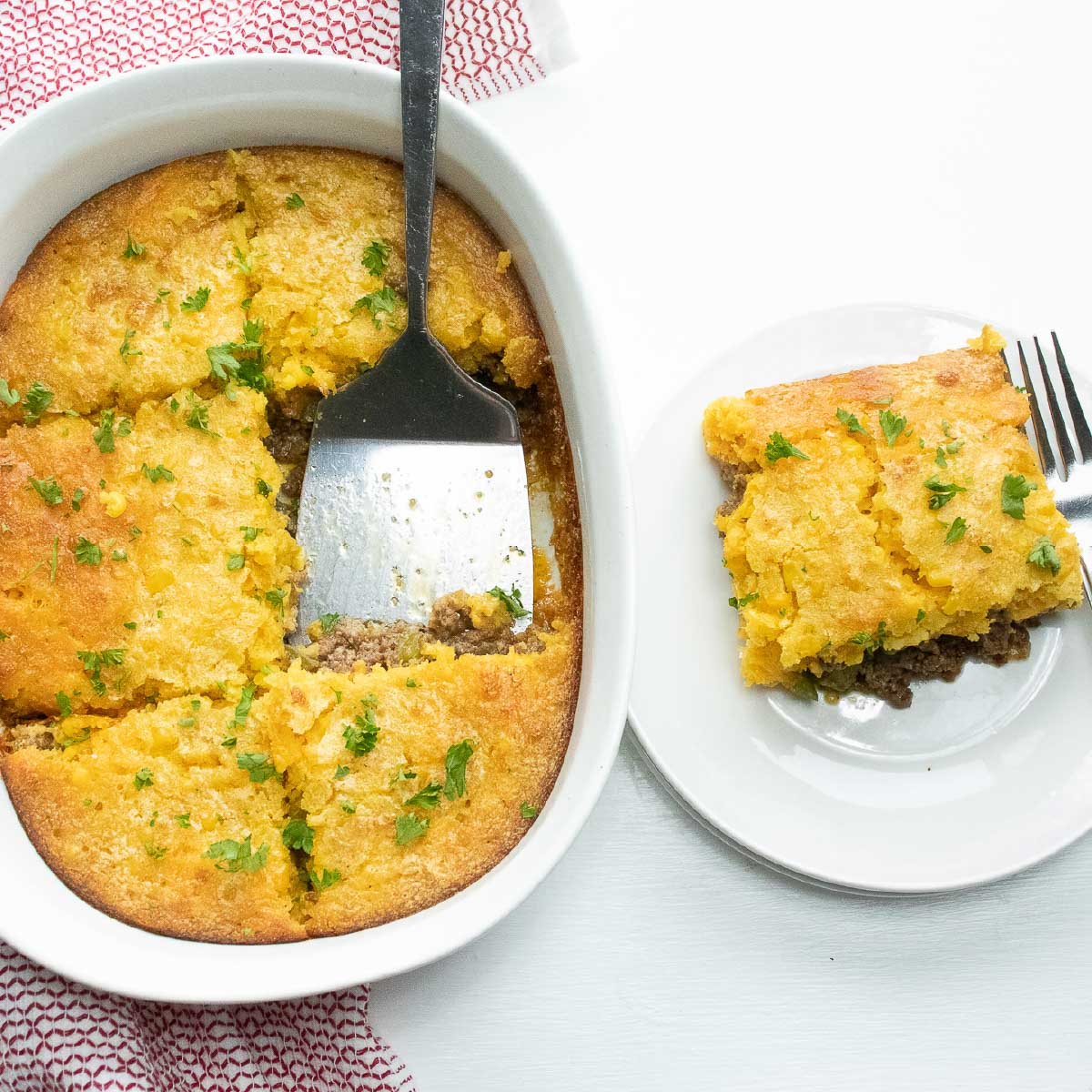 Casserole Burger Bake in a white casserole dish. One piece is cut out and sitting on a white plate next to the casserole. There is a spatula in the casserole dish and a fork on the plate.