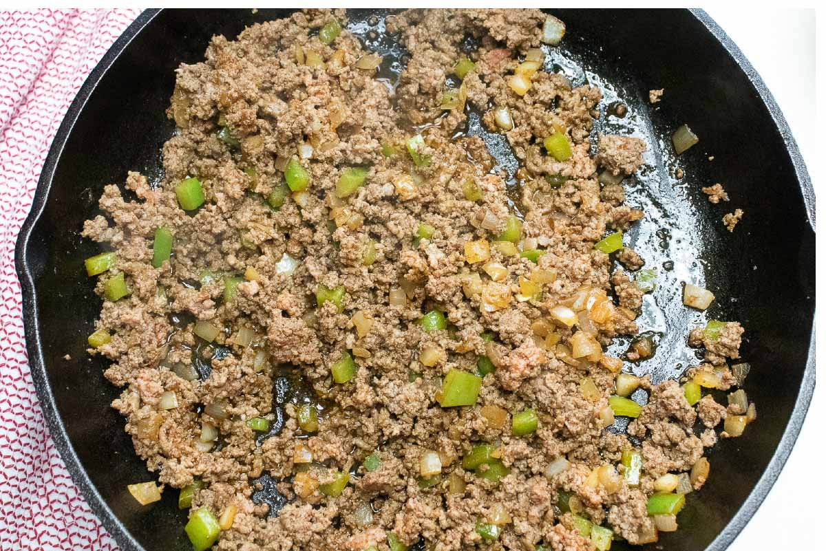 Cooked ground beef, diced onions and bell peppers in a cast iron skillet.
