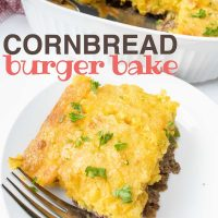 Cornbread Burger Bake in a white casserole dish. One piece is cut out and sitting on a white plate next to the casserole. There is a spatula in the casserole dish and a fork on the plate. Text is Cornbread Burger Bake Add Salt & Serve formerly Menus4Moms