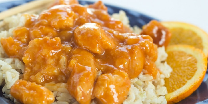 Chicken with orange sauce over rice, chopsticks, and two orange slices on a blue plate