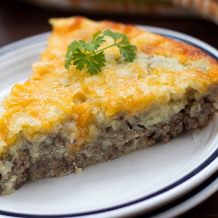White plate with slice of cheeseburger pie and sprig of parsley