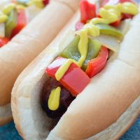Bratwurst on a hotdog bun with mustard, diced red and green bell peppers and diced onions